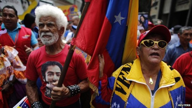 A protester carries a Venezuelan flag during a march for peace in downtown Caracas February 23, 2014