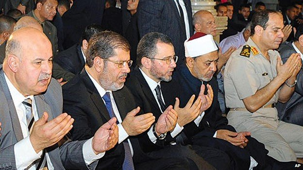 Abdul Fattah al-Sisi (far right) prays in Cairo, alongside President Mohammed Morsi (second-left)
