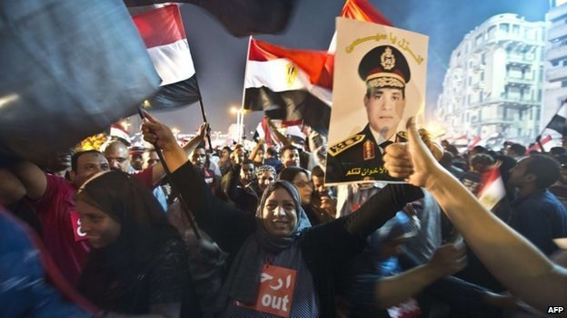 People celebrate in Cairo's Tahrir Square with a portrait of Abdul Fattah al-Sisi after the overthrow of President Mohammed Morsi on 3 July 2013