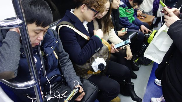 People looking at their smartphones on the Seoul underground