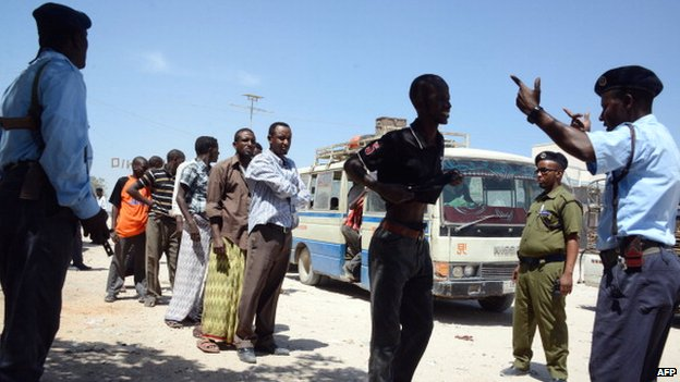 Somali soldiers frisk residents at a checkpoint in Mogadishu on February 22, 2014