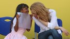 A girl talks to Colombia's pop star Shakira