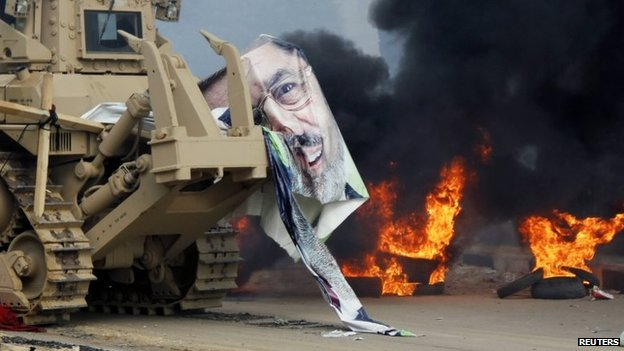 A torn poster of deposed Egyptian President Mohammed Morsi on a bulldozer as security forces clear Cairo's Rabaa al-Adawiya square (14 August 2013)