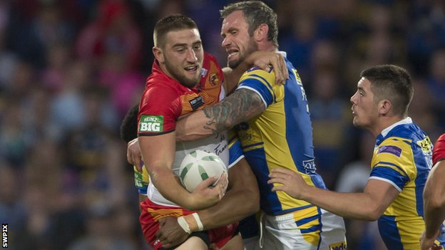 Catalan's Julian Bousquet (left) is held up by Jamie Peacock of Leeds.