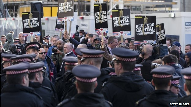 Police and protestors demonstrate outside the Old Bailey