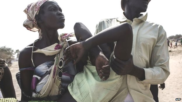 A sick person is carried to a MSF temporary hospital near a camp for displaced people in Mingkaman