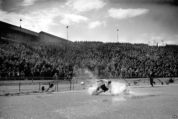 Tom Finney splashes through a puddle at Stamford Bridge in a Chelsea v Preston match in 1956