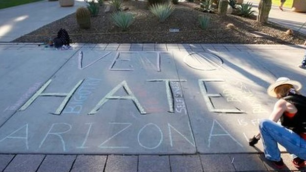 "A women writes ""veto hate Arizona"" in chalk on the sidewalk in Phoenix on 21 February, 2014"