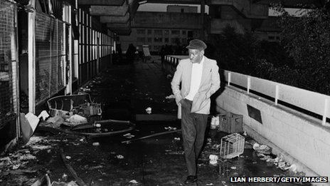 A man picks his way through the debris on a walkway on the Broadwater Farm housing estate