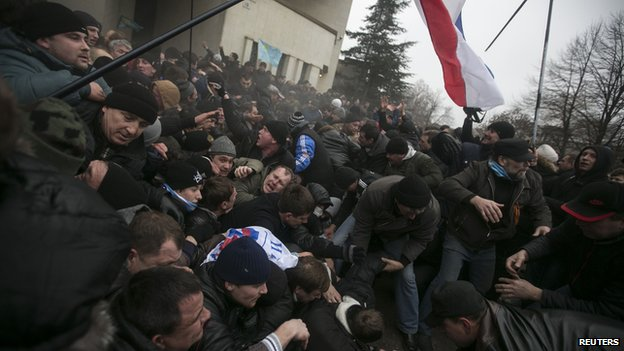 Ukrainian men help pull one another out of a stampede as a flag of Crimea is seen during clashes at rallies held by ethnic Russians and Crimean Tatars near the Crimean parliament building in Simferopol on 26 February 2014.