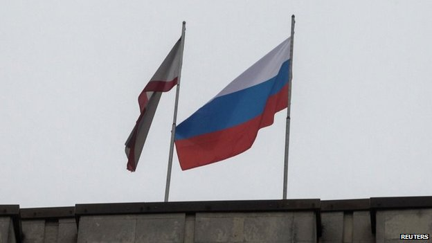 A Russian flag (R) is raised next to a Crimean flag on top of the Crimean parliament building in Simferopol