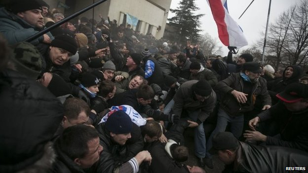 Ukrainian men help pull one another out of a stampede during clashes on Wednesday
