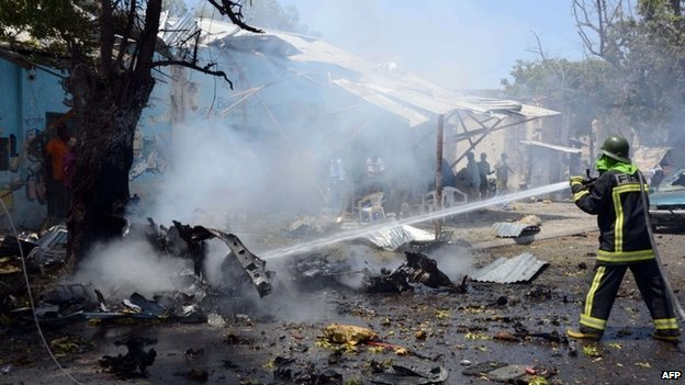 A fire-fighter hoses down the wreckage at the site where a car bomb exploded in the Somali capital Mogadishu on 27 February 2014