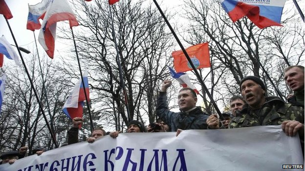 People hold flags during a pro-Russian rally outside the Crimean parliament building in Simferopol