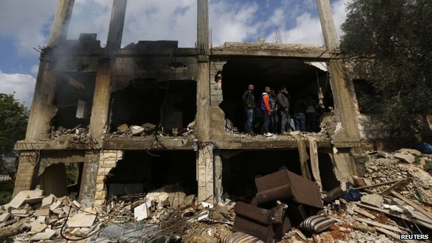 People inspect the damaged home in which Muataz Washaha was killed in Bir Zeit (27 February 2014)