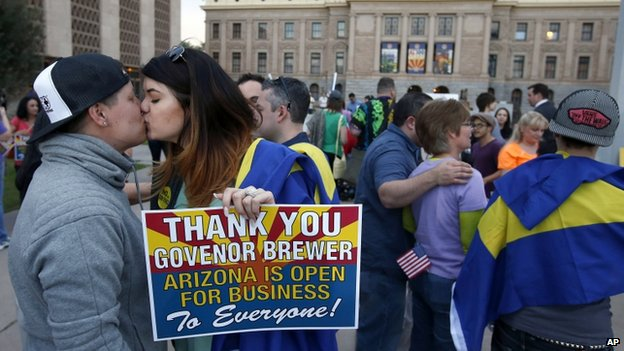 Gay rights supporters kiss after in Phoenix, Arizona, after Governor Jan Brewer vetoed an 'anti-gay' bill on 26 February 2014