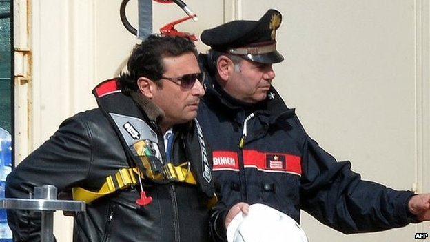 Captain Schettino (left) is escorted onboard the wrecked Costa Concordia cruise ship