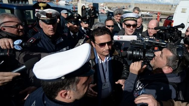 Captain Schettino (centre) is surrounded by the media after going onboard the wrecked Costa Concordia
