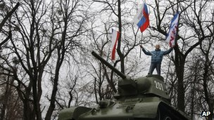 A man with a Russian and a Crimean flags stand on an old Soviet army tank in Simferopol
