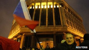 A man waves a Russian flag in front of a local parliament building during a pro-Russian rally in Simferopol, Crimea, on 27 February 2014