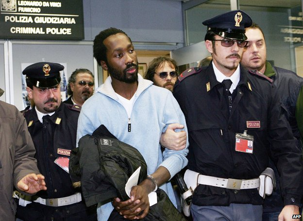 Rudy Hermann Guede (C), is escorted by police officers as he arrives at Rome's Fiumicino airport on 6 December 2007