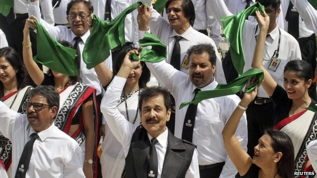 Subrata Roy (C, front) waves a green cloth with his employees after singing India's national anthem on May 6, 2013