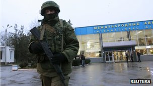 An armed man in a uniform without an insignia patrols at the airport in Simferopol