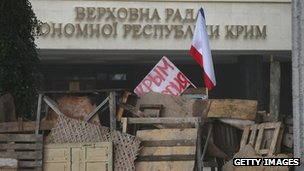 "A hand-painted sign reading ""Crimea Russia"" lies beside a flag on a barricade outside the Crimean parliament building on 28 February"