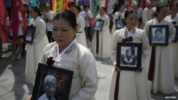 Participants carry the portraits of Korean women who were made sex slaves by the Japanese military during World War Two, during a requiem ceremony for former comfort woman Lee Yong-nyeo in central Seoul, South Korea, 14 August 2013