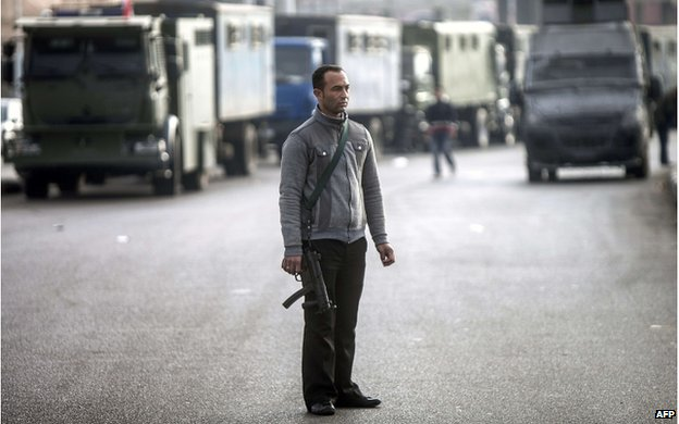 A plain-clothes policeman stands guard in the street leading to the Police Academy in Cairo