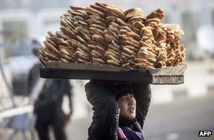An Egyptian street vendor carries a tray of pastry on his head in Cairo