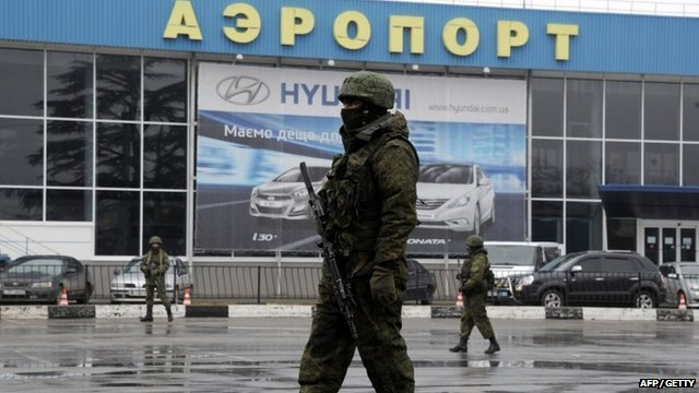 Armed men patrol outside of Simferopol airport, on February 28, 2014