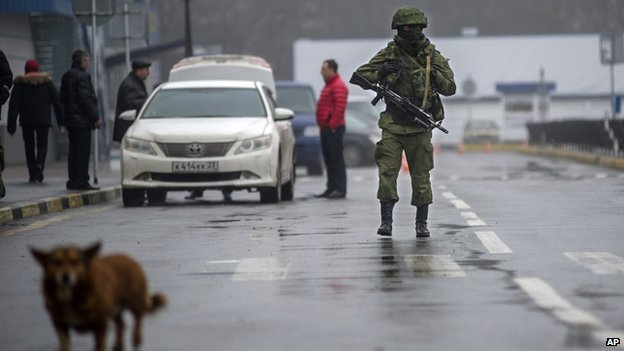 An unidentified armed man patrols a square in front of the airport in Simferopol