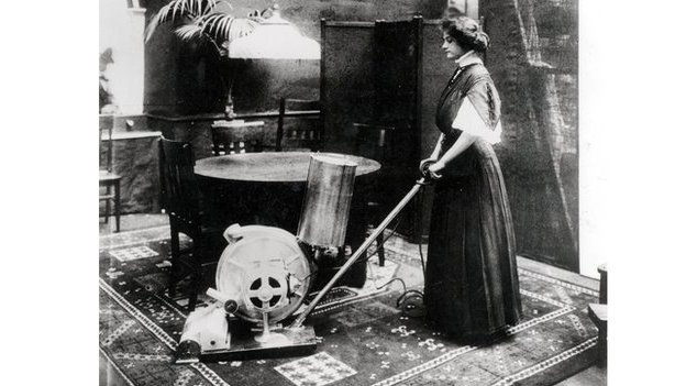A woman using an early vacuum cleaner in a dining room.