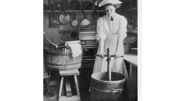 A laundry worker using a dolly stock and tub to clean clothes, prior to the invention of the washing machine.