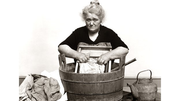 A woman washing clothes with a tub and wash board.