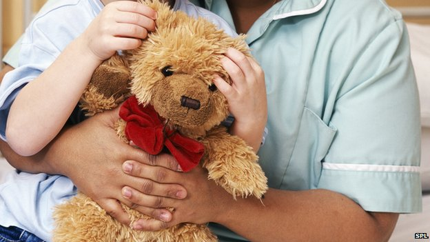 A teddy bear being cuddle by child and nurse