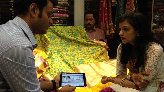 A woman and a man discussing the price of material for a sari