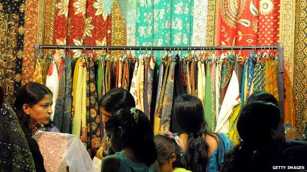 Indian women look at saris