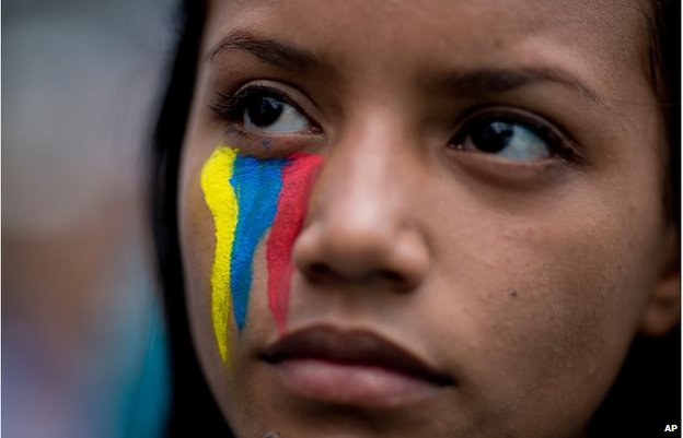 A demonstrator wearing painted stripes that represent Venezuela's national flag attends a rally with humans rights activist in Caracas, Venezuela, Friday, Feb. 28