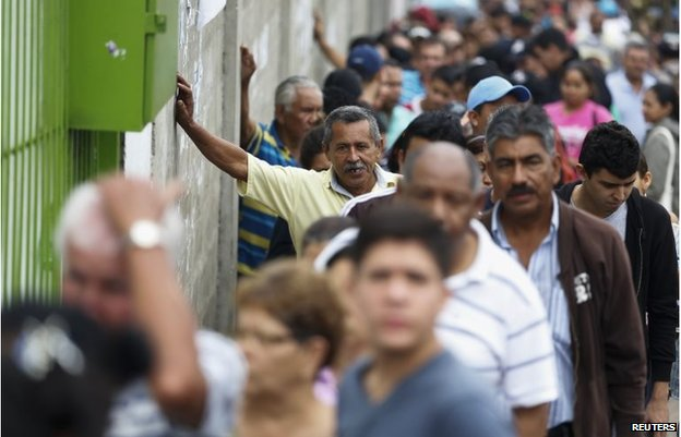 People stand in line to buy food at a supermarket in San Cristobal, about 410 miles (660 km) southwest of Caracas, February 28