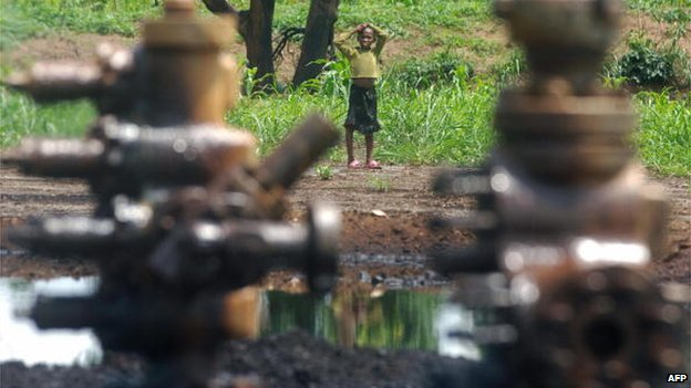 A child looks towards an abandoned oil well head leaking crude oil, 11 April 2007, in Ogoni in the Niger Delta, Nigeria