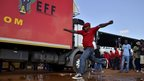 A supporter of populist South African leader Julius Malema's EFF party jumps over a puddle