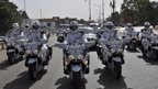 Motorcycle gendarmes escort Morocco's king and Mali's president as the king leaves after a five-day official visit