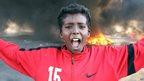 A boy gestures in front of burning tyres in Libya's second city, Benghazi