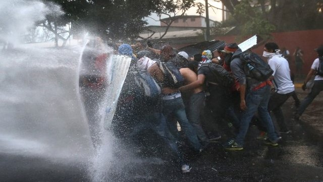Protesters hold a barricade against a water cannon fired by the Venezuelan national guard during an anti-government demonstration