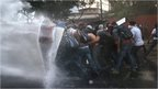 Protesters hold a barricade against a water canon fired by the Venezuelan national guard during an anti-government demonstration on February 27, 2014 in Caracas