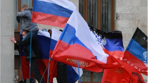 Pro-Russian activists put Russian flags over the administration office in the centre of Donetsk
