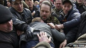 Pro-Russian protesters attack a supporter of Ukraine's new government during a rally in central Donetsk