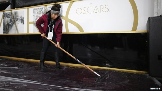 Worker sweeps water from the Oscars carpet outside Dolby Theater